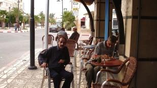 Abdelkader Benali schrijft op het terras van Espace Barbes in Taourirt in mijn notitieboekje in het Arabisch de tekst voor het huwelijk van de wolf. Naast hem mijn gids Mohammed Touzani