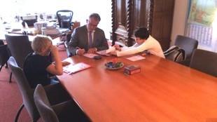 Dave Dijkman (links), burgemeester Schuiling en Diego Angevare buigen zich over de kinderpostzegels