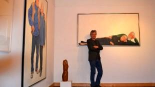 Jeroen Dercksen in de expositieruimte van de Aaltense Musea bij een portret van Erik de Vries en Hansje Snoek (foto Karin Stronks)