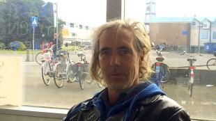 Hans de Booij in het Rob Scholte Museum met op de achtergrond Station Den Helder, ontwerp Van der Grinten, voordat het Stationsplein en het V-vormige muurtje vernield werden door Zeestad en Gemeente Den Helder (foto Staf RSMuseum)
