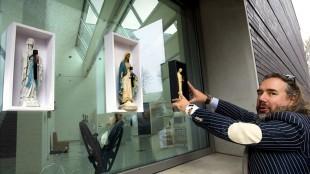 Kunstenaar Ralph Posset bevestigt zijn kunstwerkjes met Mariabeeldjes aan de ramen van het Noordbrabants Museum aan de Bossche Beurdsestraat (foto Olaf Smit)