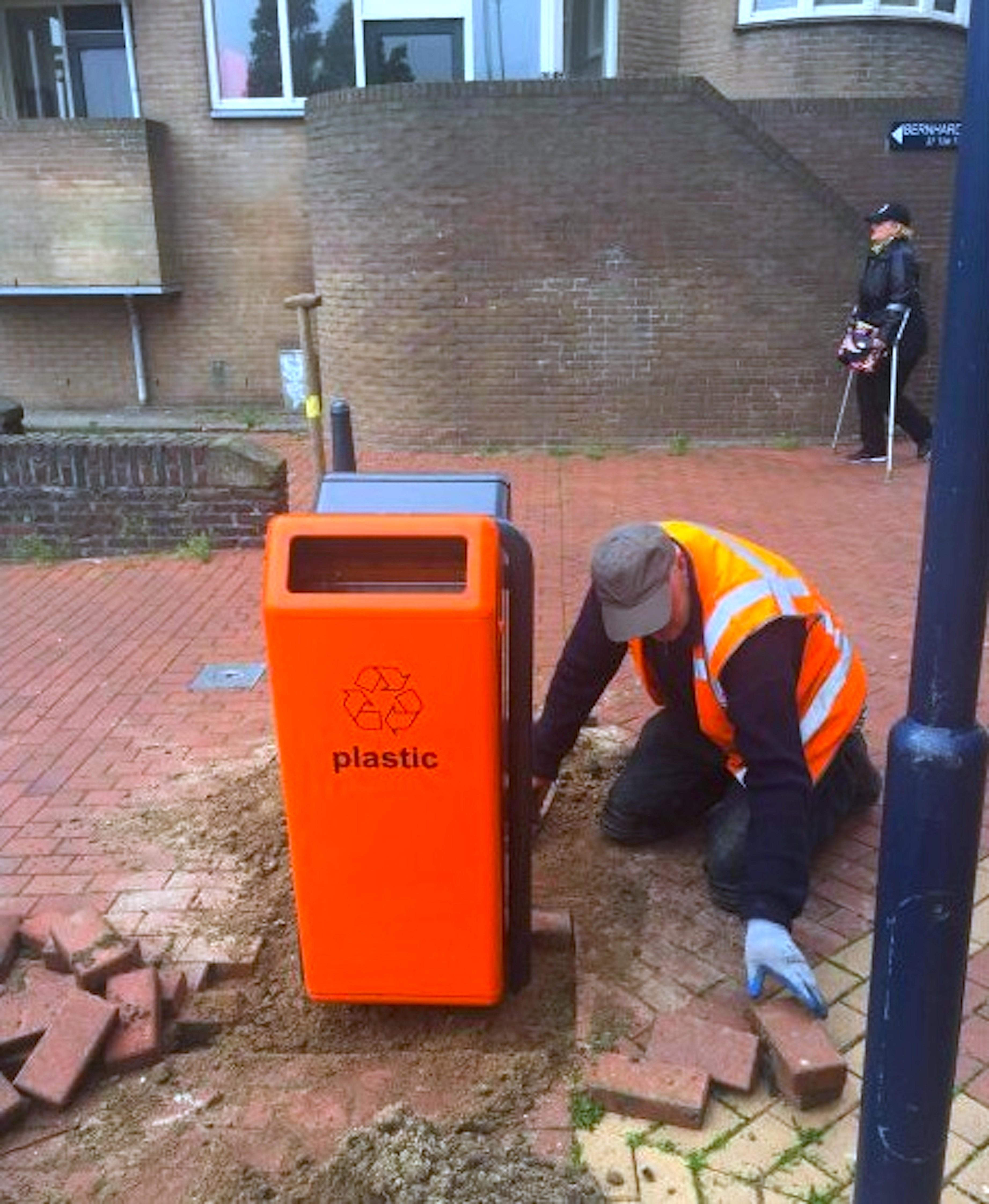 Sjouke Jorna plaatst een nieuwe afvalbak aan het Bernhardplein (foto HMC)