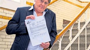 Dirk Gorter met het bewuste gemeentebesluit waarvan twee ex bestuurders beweren dat nooit ondertekend te hebben (foto Michiel van Bergen/De Telegraaf)