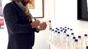 Ralph Posset signeert flesjes water (foto Twitter)