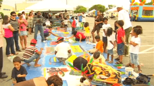 In preparation for the Longest Painting event Ashley organized a pilot, painting 50 meters with students, locals and tourists (foto YouTube)