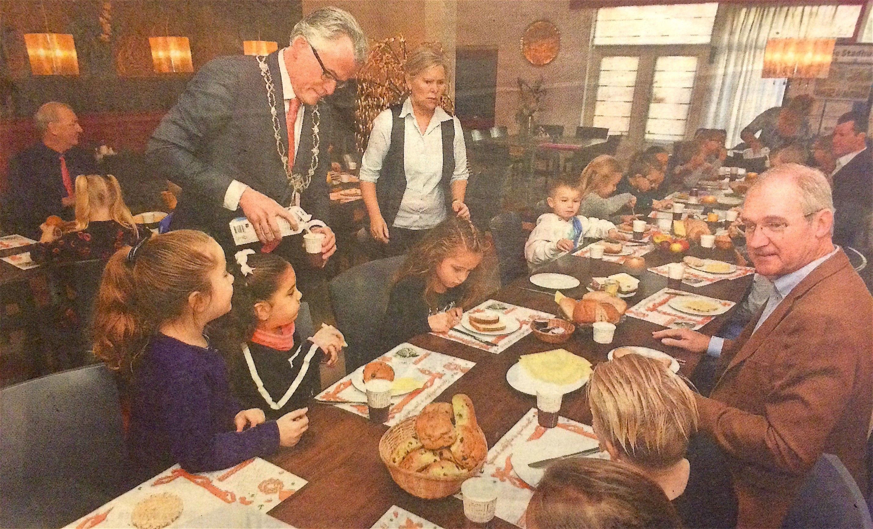 Burgemeester Schuiling schenkt melk in voor kinderen van basisschool Schoter Duijn in het restaurant van gemeente Den Helder tijdens het Nationaal Schoolontbijt (foto Helders Weekblad)