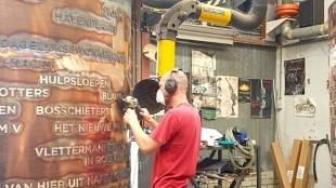 Een werknemer polijst de gelaste letters op een kolom (foto Anke de Vries)