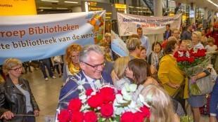 Het welkomstcomité van burgemeester Koen Schuiling met spandoeken en grote bossen rozen op Schiphol (foto Gemeente Den Helder/Peter van Aalst)