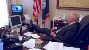 Then Vice President Dick Cheney rests his feet on his desk as he watches a live TV news report of the 9:11 attacks on the morning of September 11, 2001 (foto Flickr/U.S. National Archives)