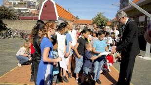 De Tuindorpschool in Den Helder voert actie voor vluchtelingenkinderen, burgemeester Schuiling neemt hun pennenvruchten in ontvangst (foto Den Helder Actueel)