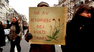 A woman holds a placard in support of the change the gilets jaunes are fighting for (foto Angela Christofilou)